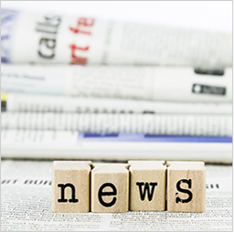 Blocks spelling out the word news placed in front of newspapers