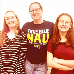 Three students pose smiling