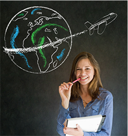 Student poses in front of a blackboard with a globe and airplane chalk design