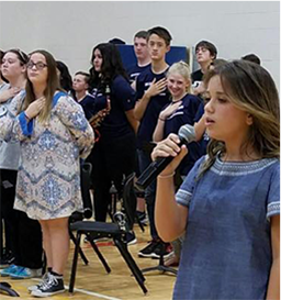 Student singing the national anthem as other students hold their hands over their heart