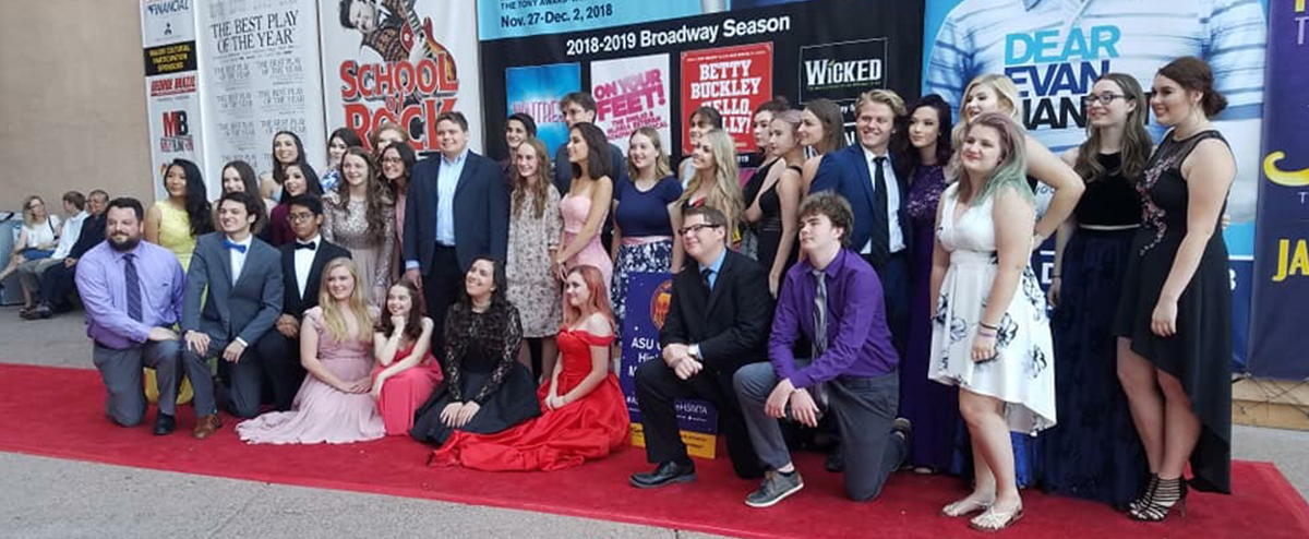 Students dressed in formal attire stand on a red carpet in front of backdrop with images and text describing the 2018 to 2019 Broadway season