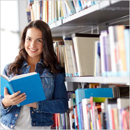 Smiling female student reads a book in the library