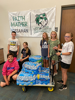 6 students standing with 6 cases of water