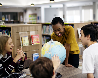 High school students talking around a globe of the earth in a classroom