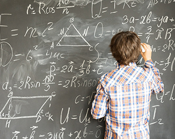 high school student working through a math problem on the chalkboard
