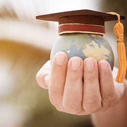 Hand holding a globe with a graduation cap