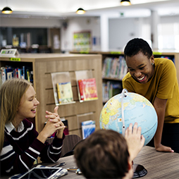 Group of students around a globe in the classroom
