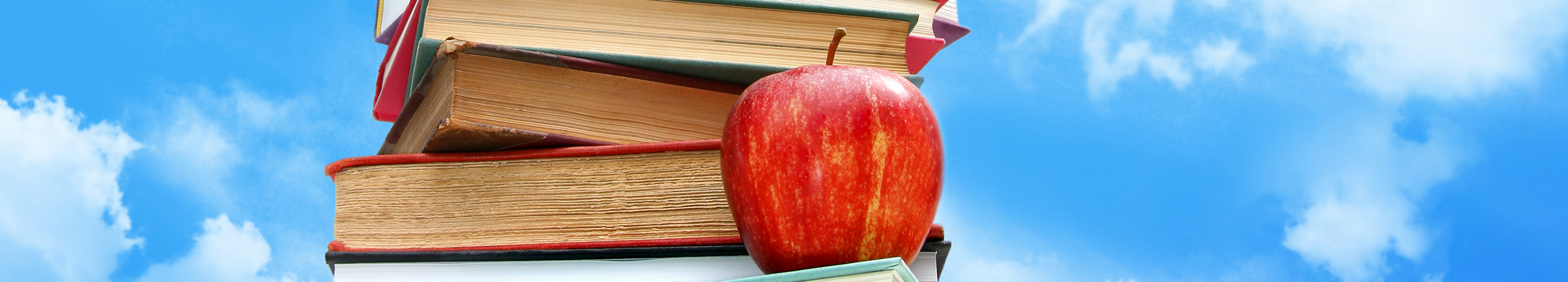 a red apple on a stack of books with a blue sky in the background