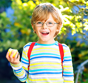 little boy holding an apple, smiling