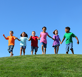 six kids running in the grass