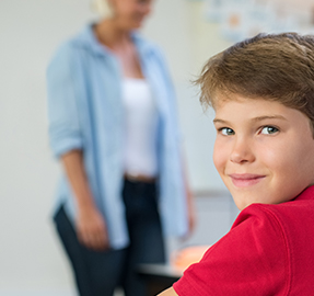 Boy smiling with a teacher in the background