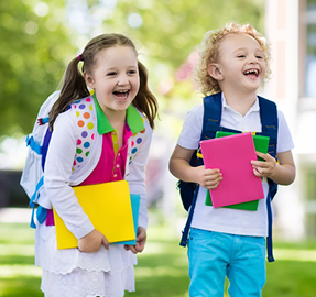 two smiling little girls wearing backpacks