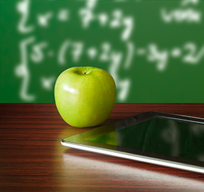 a green apple and a tablet sitting on a desk