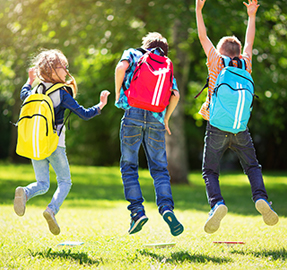 three children wearing backpacks jumping in the air