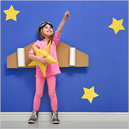 Girl dressed in airplane pilot costume holds up fist in front of a starry background