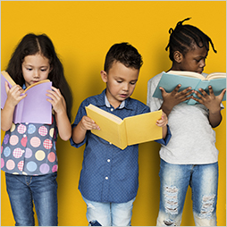 Three students read hardcover books in front of a bright background