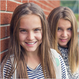 Two smiling girls pose next to a brick wall