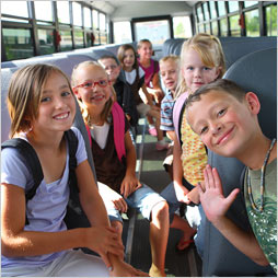 Smiling students sit in a school bus