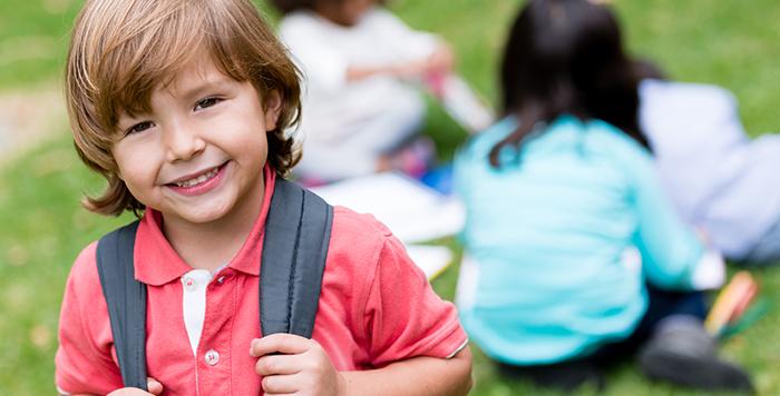 Happy preschool boy with backpack ready for school