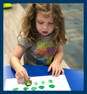 Preschooler painting with broccoli