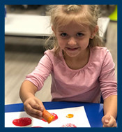 Preschool girl painting with a carrot
