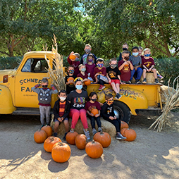 Group of cheerful students posing for picture outside with farm truck and pumpkins