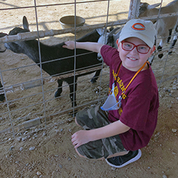 happy elementary student petting a goat