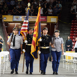 Students in uniform carrying USA flag and Arizona flag