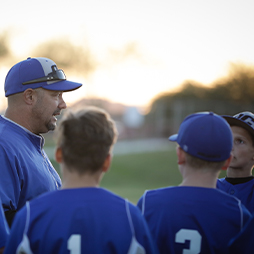 Baseball coach talking to baseball players