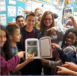 Teacher and students display a lunchbox with money