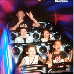 Principal in the last row of a roller coaster behind four children at Disneyland