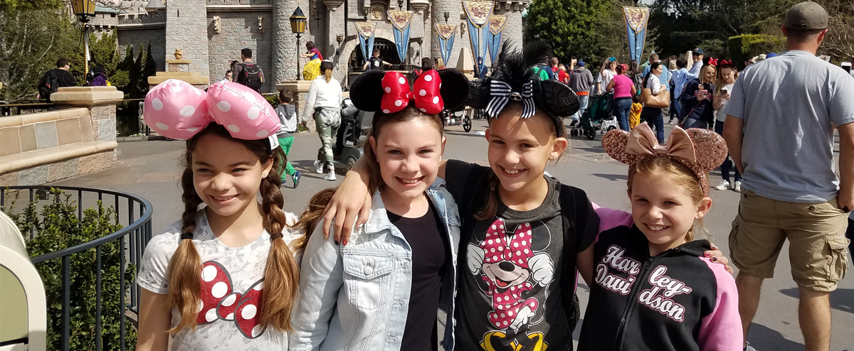 Girl students at Disneyland in front of Cinderella's Castle