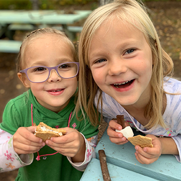 Two female students smiling with smores in their hands