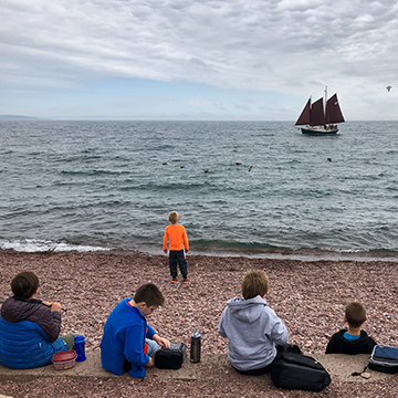 Students sitting on the beach as they watch a boat sail