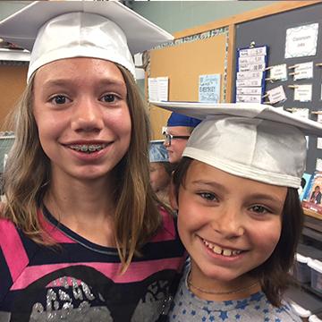 Two happy girls wearing graduation hats