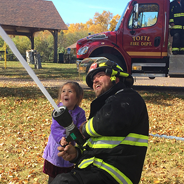 Local fireman showing amazed little girl how to use the fire hose