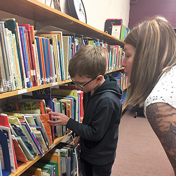 Adult helping student look for books in the library
