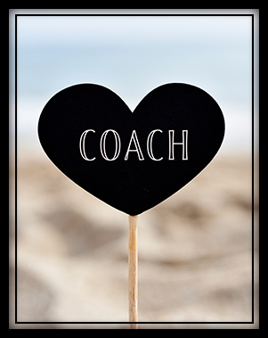 The word COACH on a black paper heart