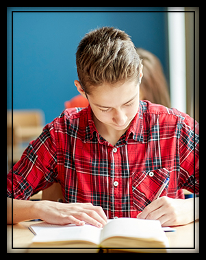 High school student in red flannel working at his desk in the classroom