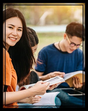 Happy female college student studying outside with classmates
