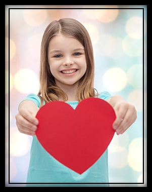 Elementary school girl holding up a red paper heart