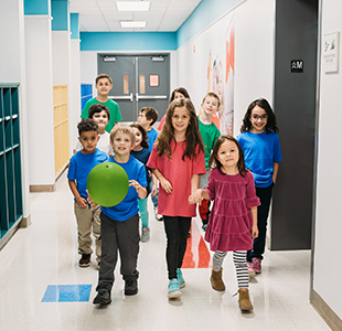 Group of happy students walking together in the school hallway