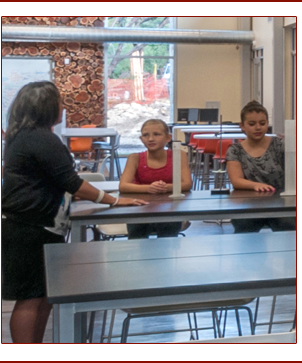 Teacher talks to two students at a table