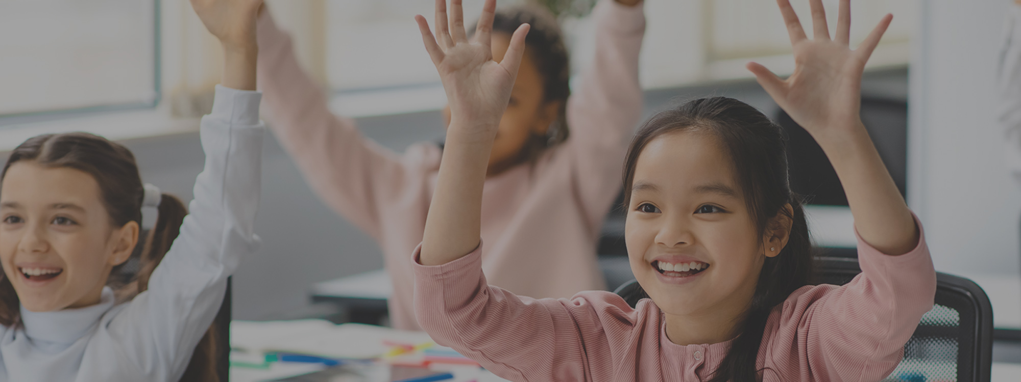 Kids smiling and raising hands in classroom
