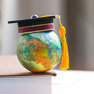 Tiny globe with graduation cap sitting on a book