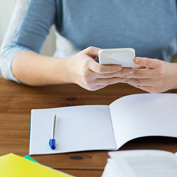 Woman at desk with mobile and notepad