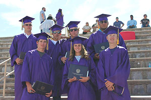 7 students in graduation gowns with diplomas