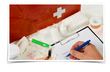 Nurse fills out paperwork next to a first aid kit